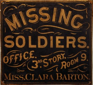 The original metal sign advertising the Missing Soldiers Office. A blue square sign with gold lettering, the sign reads: Missing Soldiers, Office 3rd Story Room 9, Miss Clara Barton